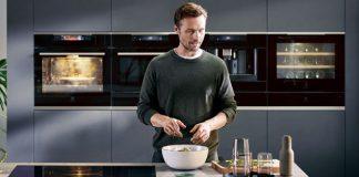 Mann richtet Salat an. Im Hintergrund sind die AEG Einbaugeräte zu sehen. Foto: AEG