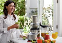 Sage Appliances the 3x Bluicer Pro SJB815 auf Küchenanrichte, Frau mit Smoothie-Glas daneben. Foto: Sage