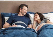 Mann mit Philips Smartsleep Snoring Relief Band um der Brust und Frau lächeln sich an. Foto: Philips