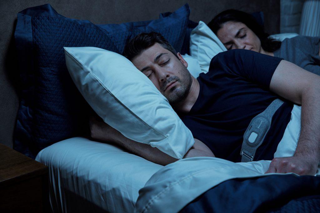 Mann mit Philips Smartsleep Snoring Relief Band um der Brust schläft. Foto: Philips