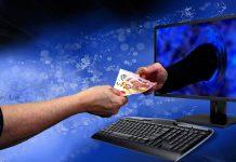 Bezahlung im Internet: zwei Hände reichen sich Geld durch den Bildschirm